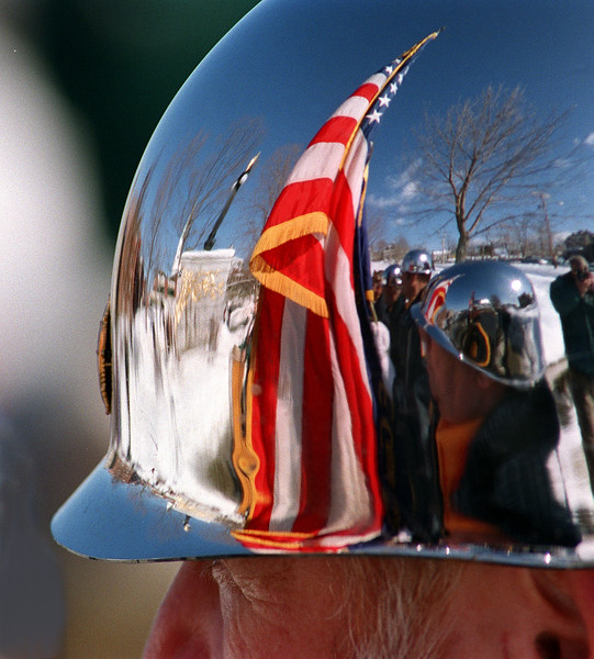 "The USS Maine monument and ""Old Glory"" are reflected in the helmet of an honor guard from Trenton VFW Post 207 during ceremonies Tuesday in Bangor.  (NEWS Photo by Bob DeLong)"