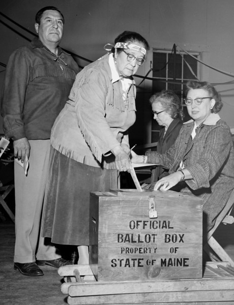 INDIANS VOTE FOR THE FIRST TIME -- Princess Watawaso of the Penobscot Indian Tribe at Old Town casts the first vote of an Indian on a reservation in Maine in 1955. The only Indians who voted previously were those who moved to cities and started paying taxes. Behind the princess is her husband, Chief Bruce Poolaw. Clerks (left to right) are Mrs. Mary Cross and Mrs. Hollis Monaghan.  (BANGOR DAILY NEWS FILE PHOTO BY DANNY MAHER)