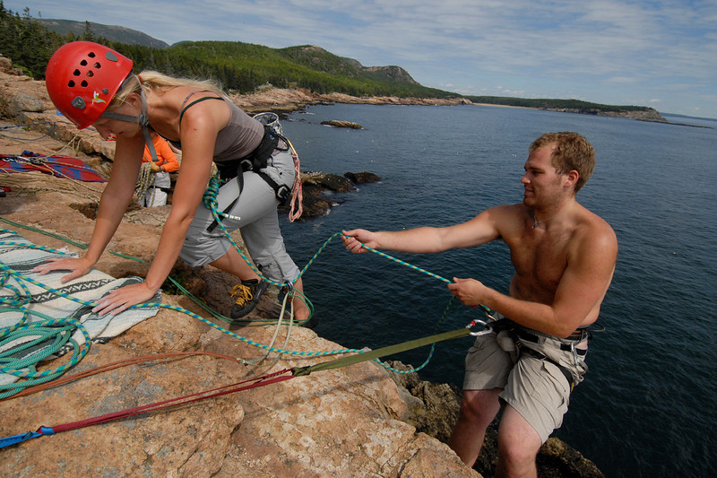 Ben Graham of Lamoine helps friend Cindi Eaton of Bangor with her line as she crests Otter Cliffs in Acadia Wednesday morning.  (BANGOR DAILY NEWS PHOTO BY JOHN CLARKE RUSS) bar harbor