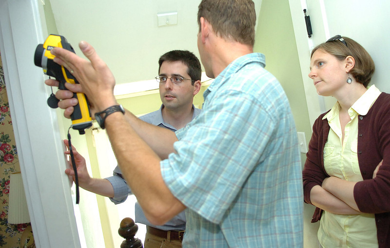 CAPTION<br /> Matthew Damon with Penobscot Home Performance (center) talks with Bangor homeowners Keith and Beth Bisson while performing a home energy audit using an infrared camera Friday, June 11, 2010. Cash incentives for those who make energy improvements to their homes this summer are available through Efficiency Maine. (Bangor Daily News/Bridget Brown)   (WEB EDITION PHOTO)