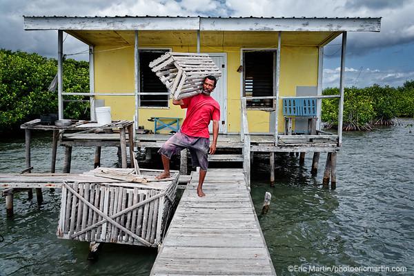 BELIZE. André le pêcheur pause avec ses cages à homard devant sa cabane de l atoll de Turneffe