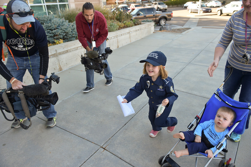 . Sidney Fahrenbruch, 4, runs up to the Longmont Safety and Justice Center, 225 Kimbark, to donate money from her piggy bank to a Longmont police officer who has cancer.  Lewis Geyer/Staff Photographer Oct. 24, 2017