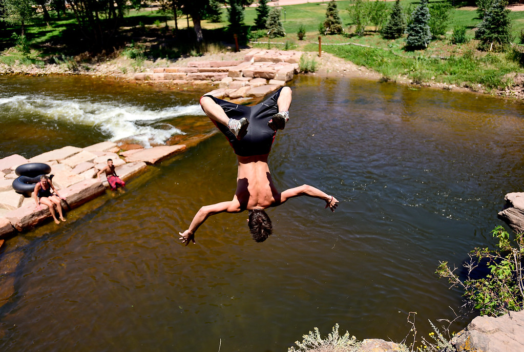 . Dominic Southworth, 17, of Longmont, flips off a rock ledge into the St. Vrain River while keeping cool at Lavern M. Johnson Park in Lyons on Wednesday.  (Matthew Jonas/Staff Photographer July 19,  2017)