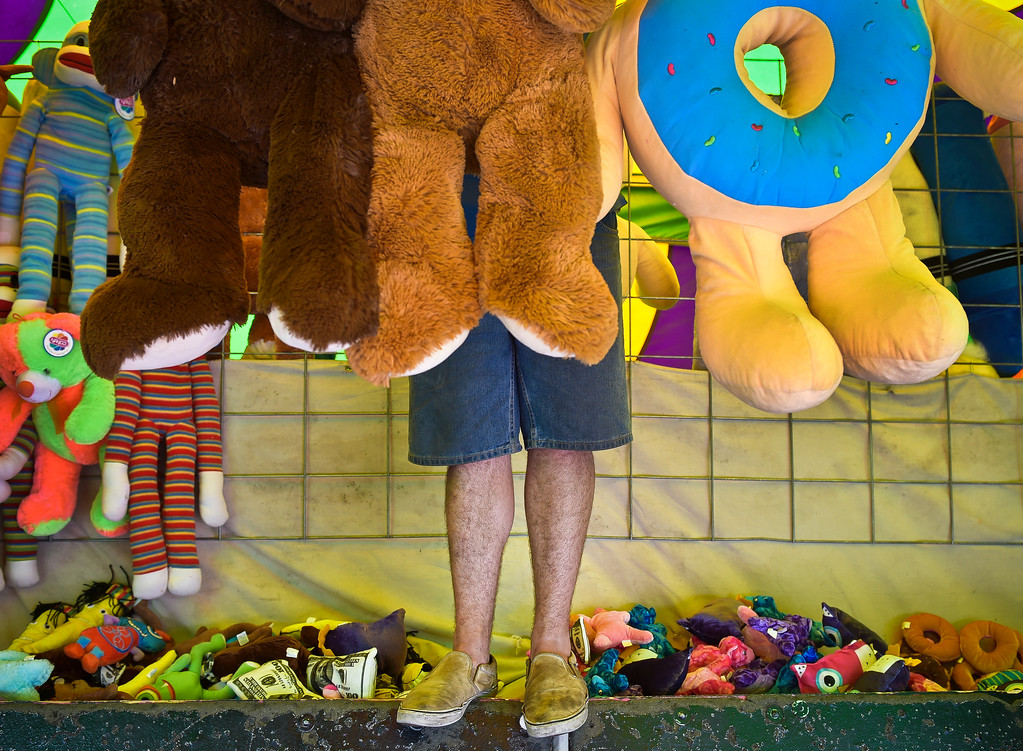 . Cody Welton hangs stuffed animals in the darts and balloons booth while preparing for the opening of the Sun Valley Rides carnival in the parking lot of the former Kmart at 21st Avenue and Main Street.  Lewis Geyer/Staff Photographer June 22, 2017