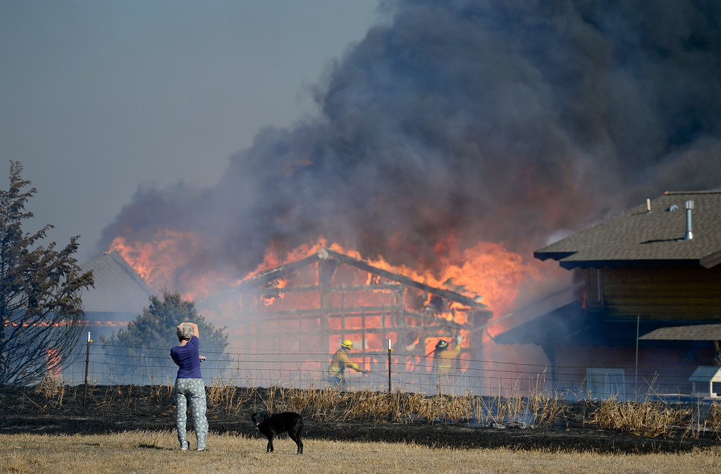 . Homeowner Joanne Larson, watches as firefighters from multiple departments work to contain a grass fire that caught her garage/workshop and vehicles on fire in Weld County on Monday. More photos: Times-Call.com. (Matthew Jonas/Staff Photographer Feb. 20,  2017)