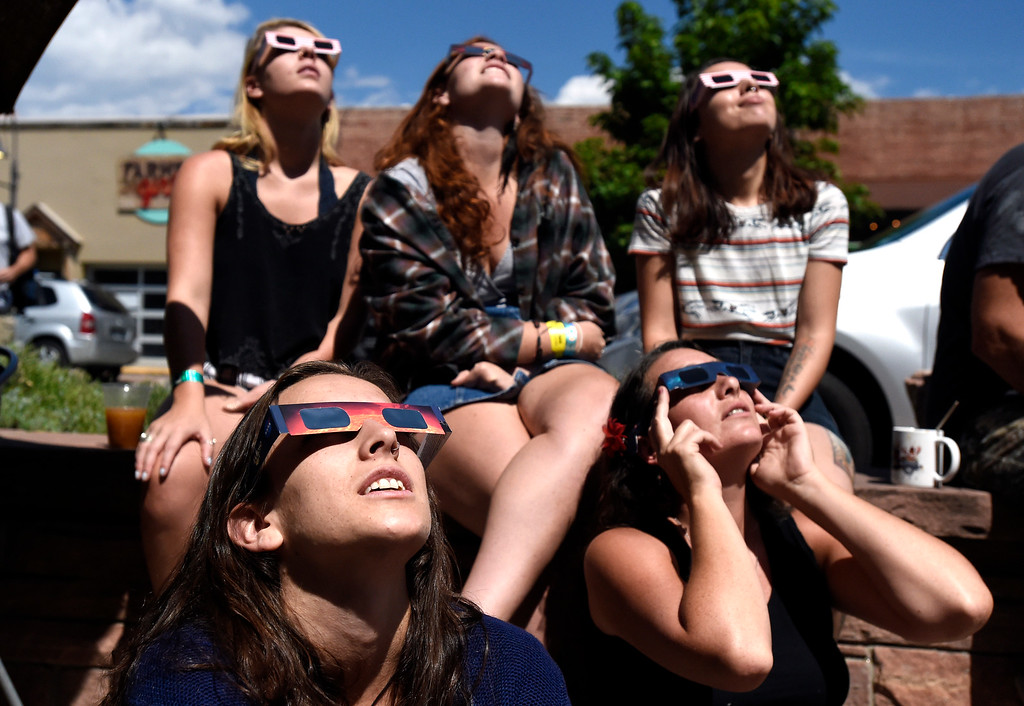 . Maya Guffey, at left front, Amanda Anderson, Jade Leveille, Kimy Harrison and Marsena Martinez look at the Solar Eclipse on Main Street on Monday, Aug. 21, in Lyons, Colorado. Jeremy Papasso/ Staff Photographer/ Aug 18, 2017