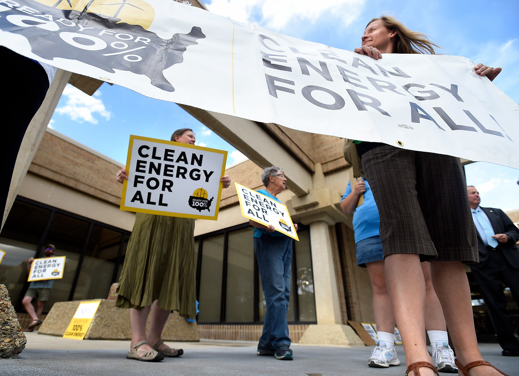 . Sustainable Resilient Longmont members Pam Leland, at left, Judith Blackburn and Trista Rucks hold signs during a rally outside of the City Council Meeting on Tuesday on Kimbark Street in Longmont. For more photos of the rally go to www.dailycamera.com Jeremy Papasso/ Staff Photographer/ June 13, 2017