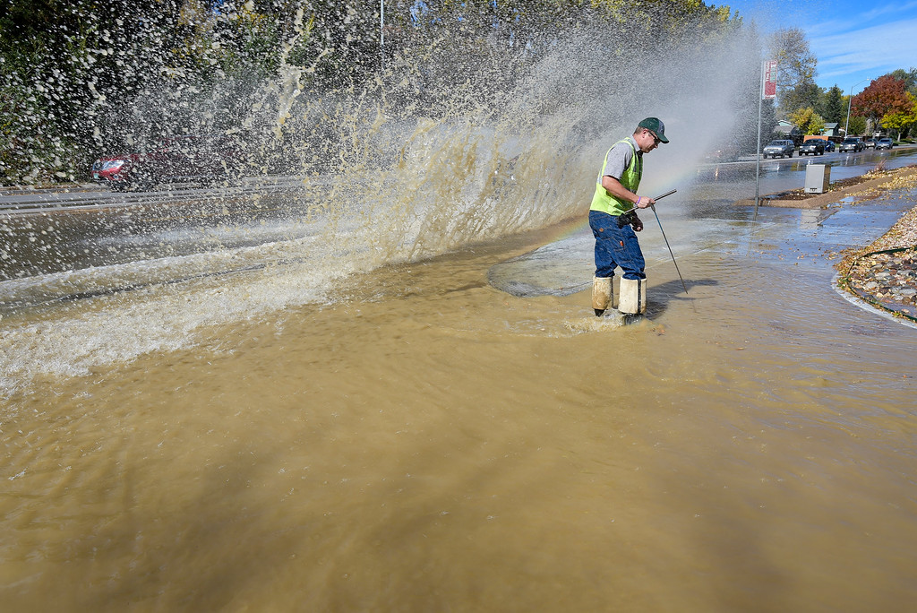 . A City of Longmont employee who refused to be identified is splashed by a passing car while searching for a valve at the scene of a water main break on 11th Avenue at Hover Street. Lewis Geyer/Staff Photographer Oct. 16, 2017