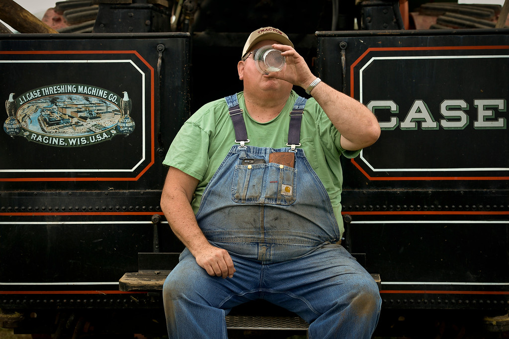 . Steve Montgomery, of Firestone, keeps cool while sitting on the back step of a 100-year-old steam tractor during the Yesteryear Farm and Home Show at the Dougherty Museum, 8306 N. 107st. Lewis Geyer/Staff Photographer August 25, 2017