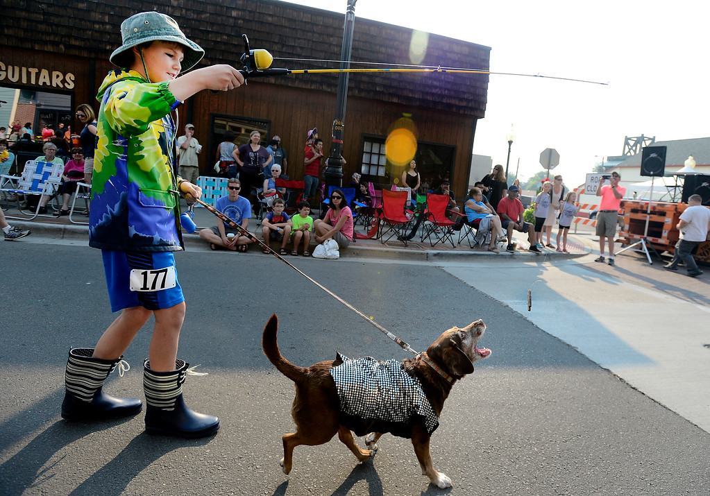 . Willy Mitchell, 10 gets his dog moving with a dog treat on a fishing line in the Pet Parade at the Labor Day Parade in Louisville on Monday Sept 4 2017.  For more photos and video go to daily camera.com Paul Aiken Staff Photographer