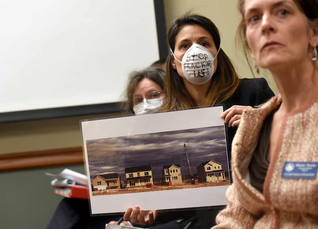 . Lauren Petrie, with Food and Water Watch, wears a mask and holds a photograph of a fracking site near residential homes during a public meeting on Monday with the Colorado Oil & Gas Conservation Commission  on Monday at the COGCC corporate office in Denver. The meeting gave citizens a chance to voice opinions on proposed spacing applications by Extraction Oil & Gas in Broomfield. For more photos and video of the meeting go to dailycamera.com Jeremy Papasso/ Staff Photographer/ Oct. 30, 2017