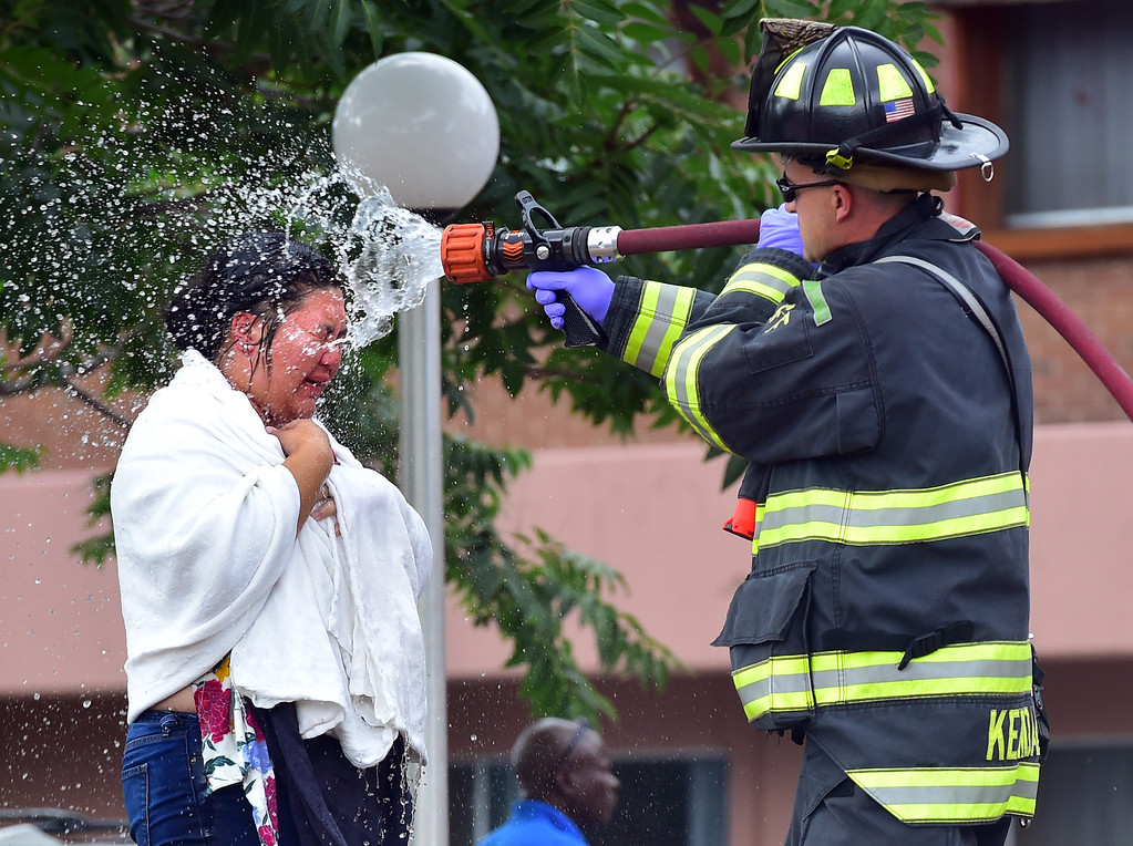 . A woman is sprayed down by a firefighter at Mesa Vista of Boulder on Wednesday afternoon.  Paul Aiken Staff Photographer Sept 13 2017