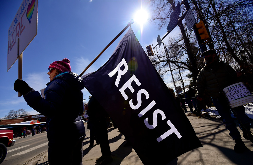 . A woman who declined to give her name holds a large flag with the word \'resist\' on it and a sign with the words \'all are welcome here\' on it while demonstrating along Main Street in Longmont on Saturday. More photos: TimesCall.com. Matthew Jonas/Staff Photographer Feb. 25,  2017