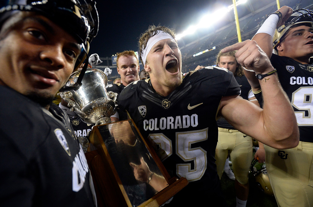 . Shay Fields, left, and Ryan Moeller celebrate getting the Centennial Cup after beating CSU at the Rocky Mountain Showdown in Denver.  Cliff Grassmick / Staff Photographer/ September 1, 2017