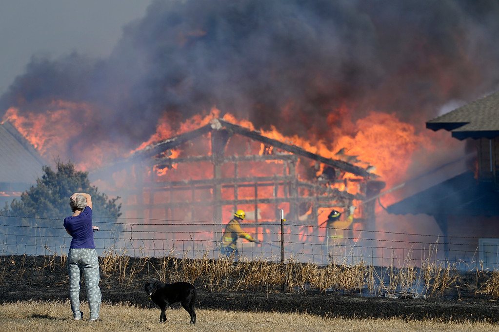 . Homeowner Joanne Larson, watches as firefighters from multiple departments work to contain a grass fire that caught her garage/workshop and vehicles on fire in Weld County on Monday. More photos: Times-Call.com. Matthew Jonas/Staff Photographer Feb. 20,  2017