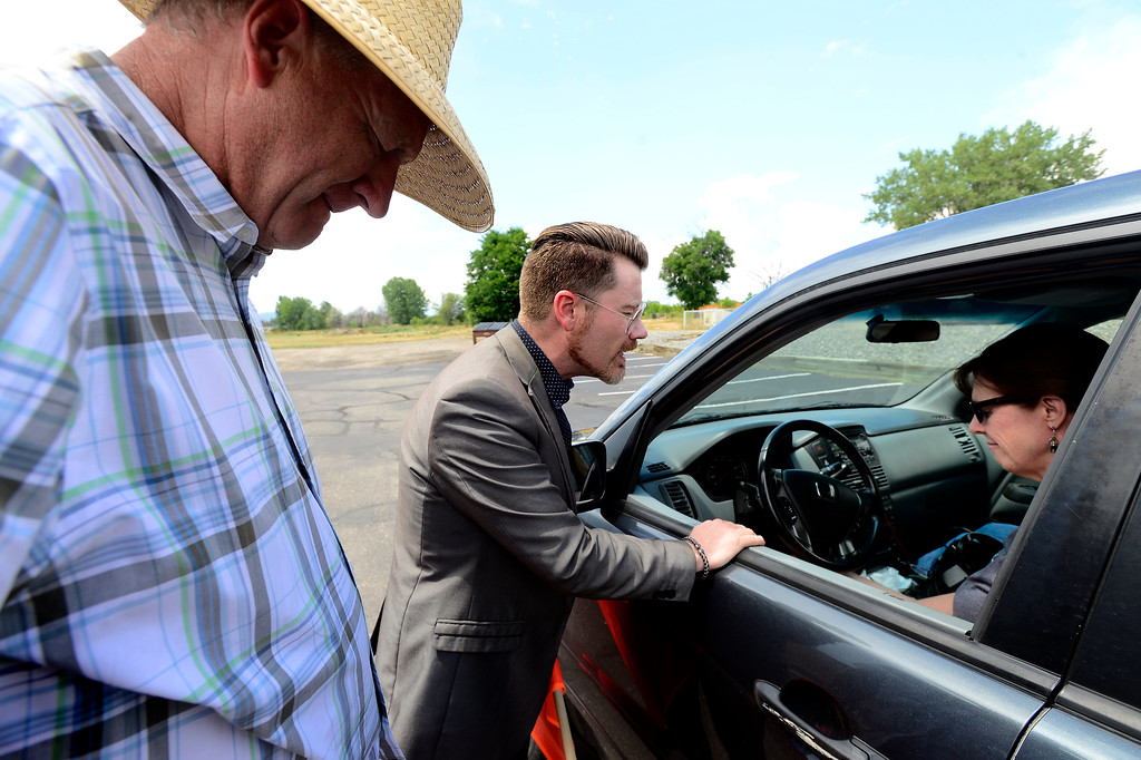 . Pastors Jimmy Ratzlaff, at left, and Brandon Kolb pray with Dara Warde during the City on the Hill Church\'s drive thru prayer on Sunday.  For more photos go to dailycamera.com Paul Aiken Staff Photographer July 23, 2017