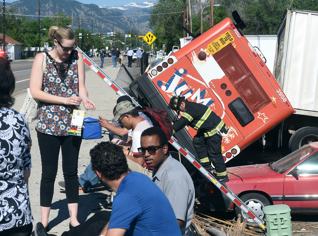 . Bus passengers fill out paperwork after being checked by medical personnel. An RTD Jump-line bus was involved in a multi-vehicle crash this morning that is slowing traffic in the 6500 block of Arapahoe Road. The bus rolled over into a RV and boat parking storage area. There were minor injuries. For more photos, go to www.dailycamera.com.  Cliff Grassmick  Staff Photographer June 21, 2017