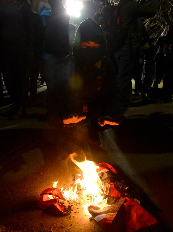 . A protester kneels near a burning rebel flag outside of the Mathmatics building during the Milo Yiannopoulos speech on Wednesday, Jan. 25, on the University of Colorado campus in Boulder, Colo. Jeremy Papasso/ Staff Photographer/ Jan. 25, 2017