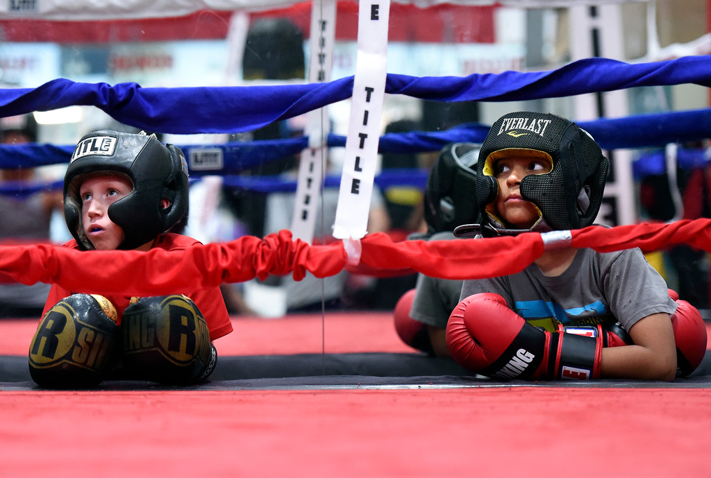 . Austin Mathis, 7, at left, and Elijah Cortes, 9, watch a sparring match in the ring during an after-school boxing class for kids on Thursday at La Familia Boxing inside the YMCA in Longmont. For more photos and video of the after-school boxing program go to www.timescall.com Jeremy Papasso/ Staff Photographer/ May 11, 2017
