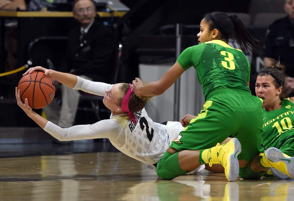 . Colorado\'s Alexis Robinson, left, stretches out for a loose ball with Oregon\'s Justine Hall and Lexi Bando on the floor during the first half of the February 19, 2017 game in Boulder, Colorado. Cliff Grassmick / Staff Photographer / February 19, 2017