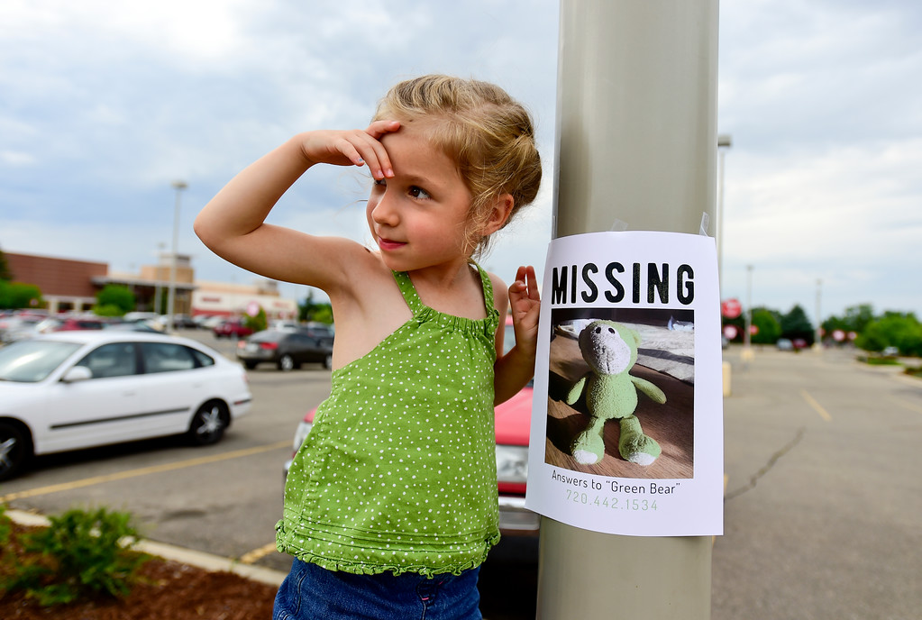 ". Ellie Pinkerton, 3, with help from her father Mark Pinkerton (not pictured) hang ""missing\"" posters for a lost green bear in a parking lot on the 500 Block of South Hover Street in Longmont on Tuesday. The Pinkertons believe it was the last known place the green bear was seen. Matthew Jonas/Staff Photographer July 11,  2017"