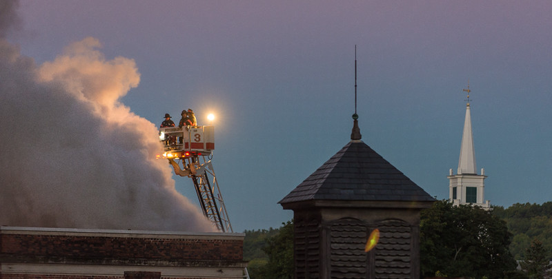 Smoke billows from the roof of the former BF Brown School as Fitchburg Firefighters man one of the TowerLadders at dawn, with the steeple of First United Parish in the backround. SENTINEL&ENTERRPISE/ Jim Marabello