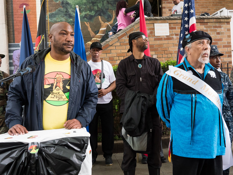 At the parade's end, Jelani Mashariki of Black Veterans For Social Justice addressed the crowd. To his right, the parade's Grand Marshall, Chief Dwayne C. Perry, of the Ramapough Lenape Nation. Perry is a Native American veteran.