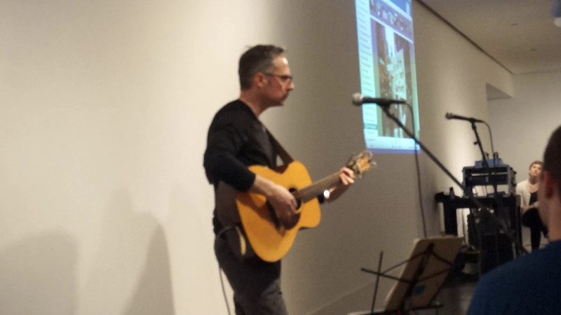 Press PLAY ► (above) to see a short video.<br /> <br /> Singer-Songwriter John Munnelly captivated the audience with his songs of peace and love.