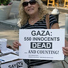 Stacey holds a sign that's already outdated. Over 700 have died thus far.