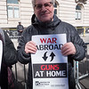 Eric holds a BFP sign that connects militarism and gun violence.