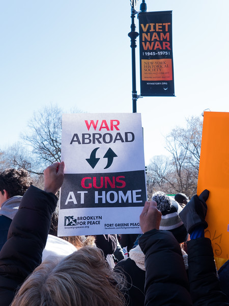 Advertising banners on the lamppost for a NY Historical Society exhibit on the Vietnam war are set off by a marcher's  sign connecting war s abroad to gun violence at hom.