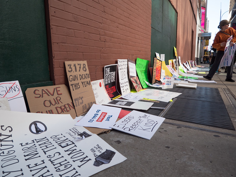 Hundreds of signs left against a building on West 45th Street at the end of the march.