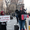 "Emily Rubino of Peace Action, addresses the protest. The young Yemeni woman hold a sign that says in Arabic: ""You can't take it with you."" That alludes to the trillions of oil dollars of the bin Salman family (the despotic ruling family of Saudi Arabia). In the end, all your trillions cannot be take with you when you die."