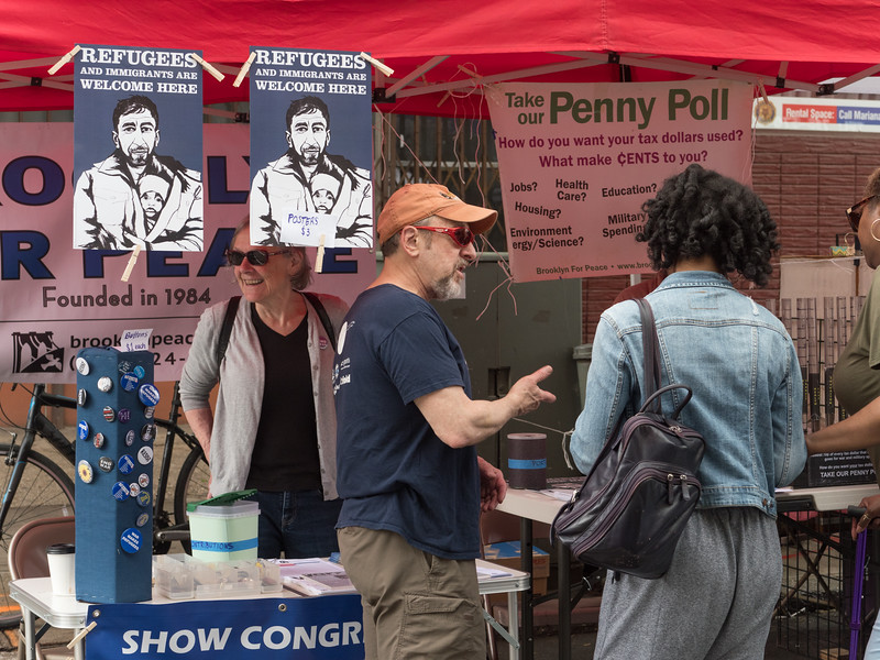 Sam explains the Penny Poll to a passer by. The table was very popular with Street Fair strollers and close to a thousand flyers were distributed.