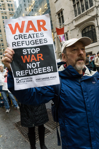 Sam holds a BFP sign aloft. It connects the cause and effect relationship of war and refugee crises.