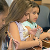 Douglas Siqueira a music teacher from Indian Hill Music taught a ukulele class at the Boys and Girls club on Wednesday, July 24, 2019. Suhaly Rosado, 9 from Fitchburg, Jennie-Lynn Abdurraheen, 11 center, from Fitchburg and Camila Santiago, 8, from Fitchburg try and learn to play Twinkle Twinkle Little Star during the workshop. SENTINEL & ENTERPRISE/JOHN LOVE
