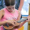 Douglas Siqueira a music teacher from Indian Hill Music taught a ukulele class at the Boys and Girls club on Wednesday, July 24, 2019. Sammy Morrison, 10, from Clinton tries to strum the right strings as she learns to play Twinkle Twinkle Little Star during the workshop. SENTINEL & ENTERPRISE/JOHN LOVE
