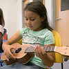 Douglas Siqueira a music teacher from Indian Hill Music taught a ukulele class at the Boys and Girls club on Wednesday, July 24, 2019. Camila Santiago, 8, from Fitchburg tries to strum the right strings as she learns to play Twinkle Twinkle Little Star during the workshop. SENTINEL & ENTERPRISE/JOHN LOVE