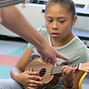 Douglas Siqueira a music teacher from Indian Hill Music taught a ukulele class at the Boys and Girls club on Wednesday, July 24, 2019. Suhaly Rosado, 9, from Fitchburg gets some instructions from Siqueira as she tries to strum the right strings while learning to play Twinkle Twinkle Little Star during the workshop. SENTINEL & ENTERPRISE/JOHN LOVE