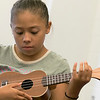 Douglas Siqueira a music teacher from Indian Hill Music taught a ukulele class at the Boys and Girls club on Wednesday, July 24, 2019. Suhaly Rosado, 9, from Fitchburg tries to strum the right strings as she learns to play Twinkle Twinkle Little Star during the workshop. SENTINEL & ENTERPRISE/JOHN LOVE
