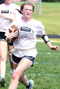 Will Fehlinger | The Herald-Tribune Liz Heidlage carries the pigskin for the junior class during this year's powder puff football game.