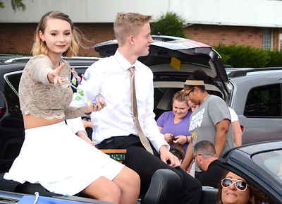 Will Fehlinger | The Herald-Tribune Junior Madison Chambers, escorted by Jacob Nobbe, sends a handful of candy to the street during Batesville's homecoming parade Sept. 21.