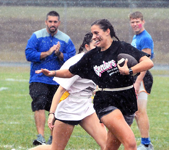 Will Fehlinger | The Herald-Tribune Batesville senior Carlie Werner carries the ball through a driving rain at Friday's powder puff football contest.