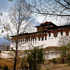 Paro Dzong (Rinpung Dzong:) (Fortress Monastery) Is one of Bhutan's most impressive and well known monasteries and perhaps the finest example of Bhutanese architecture. It is visible throughout the valley, and was constructed in 1646. The Dzong was used on numerous occasions to defend the valley from invasions by Tibet. Like most dzongs it houses both the monastic body and district government offices, including the local courts.  Dzongs-Fortress Monasteries are often located in strategic hilltops, are among the finest examples of Bhutanese architecture commanding most of Bhutan's valleys. They were built to consolidate power and control and play a similar role to castles in the west. They protected the surrounding villages from Tibetan army invasions of the district and they still continue to house government offices as well as the monk body of a district. The magnificent scale and proportions of the dzongs and the ingenious manner in which they have been built makes them unique. Most were built in the 17th century and are massive complexes, with slopping walls, ornate wood work and pitched roofs. Incredibly not a single nail was used in the construction of these great buildings. The paintings and the statues representing religious figures are exceptional. The red band, called Khemar that we see in the dzongs and the chortens, symbolizes the religious character of the buildings.