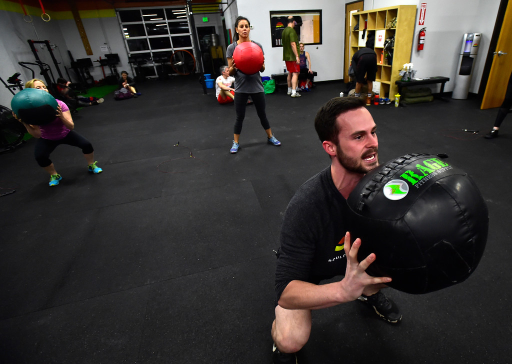 . BOULDER, CO. NOVEMBER 14, 2018 Instructor Wesley Martin demonstrates the proper position for a warmups he wants in advance of doing the Wall Ball exercise as part of the BLDR30 workout at Boulder Athletics in Boulder on Wednesday.  For more photos go to dailycamera.com  (Photo by Paul Aiken/Staff Photographer)