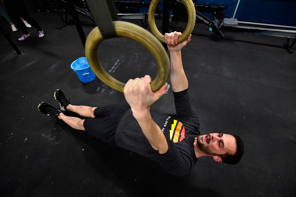 . BOULDER, CO. NOVEMBER 14, 2018 Instructor Wesley Martin demonstrates the proper position for Ring Row exercise as part of the BLDR30 workout at Boulder Athletics in Boulder on Wednesday.  For more photos go to dailycamera.com  (Photo by Paul Aiken/Staff Photographer)