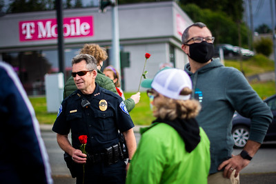 Port Angeles Police Chief Brian Smith holds a rose as he speaks with Black Lives Matter protesters, including Port Angeles Mayor Kate Dexter and City Council Member Mike French, on Friday, June 5, 2020. (Jesse Major)