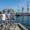 A couple of cyclists visiting from Baltimore stand on the water-front of the town of Pictou with the ship Hector and the Hector Heritage Quay in the background.