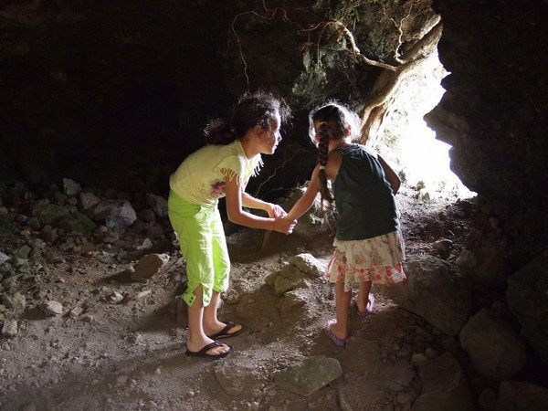 Girls exploring a lava cave on the Big Island of Hawaii