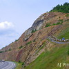 The Sideling Hill road cut is a 340-foot deep notch excavated from the ridge of Sideling Hill for Interstate 68, about 6 miles west of Hancock in Washington County, Maryland. It is notable as an impressive man-made mountain pass, visible from miles away and is considered one of the best rock exposures in Maryland and the entire northeastern United States. Almost 810 feet of strata in a tightly folded syncline are exposed in this road cut. Although other exposures may surpass Sideling Hill in either thickness of exposed strata or in quality of geologic structure, few can equal its combination of both. (This and next two photos.)